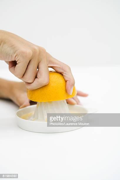 Woman juicing orange, cropped view, close-up