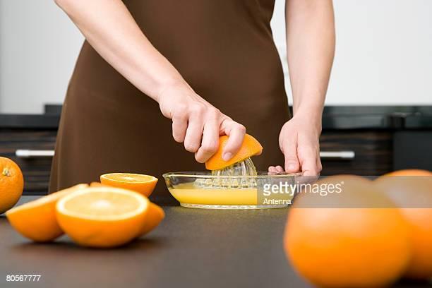 A woman juicing oranges