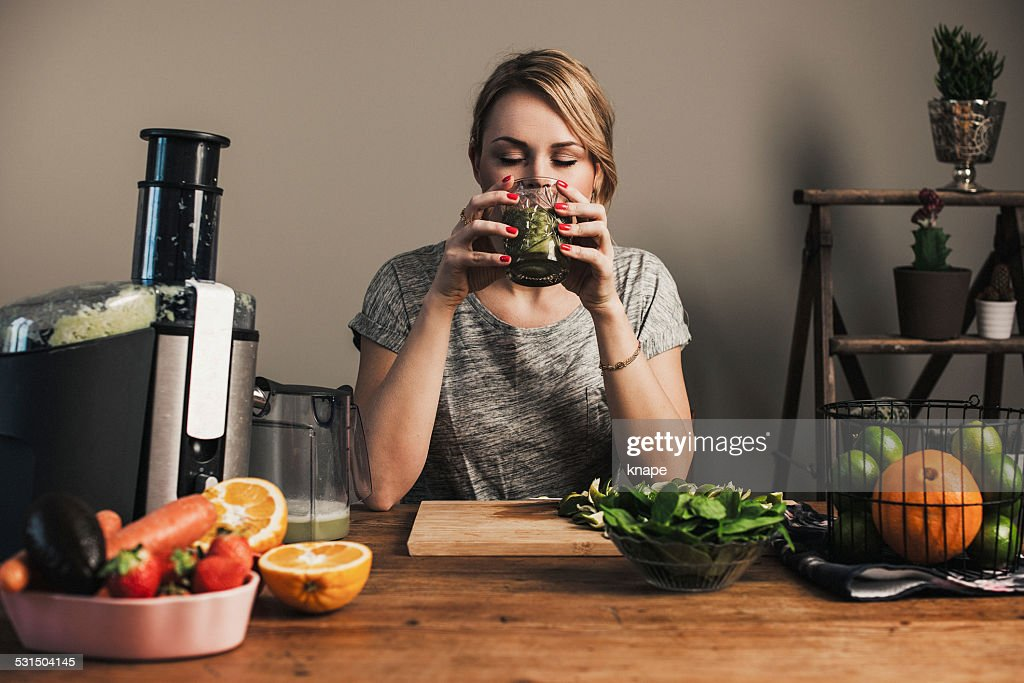 Woman juicing with fresh fruit : Stock Photo