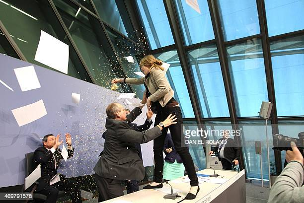 A woman jumped on the table throws papers and confetti as she interrupts a press conference by Mario Draghi President of the European Central Bank...