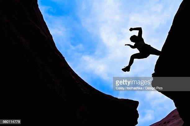 woman jumping across a canyon gap - slot canyon stock pictures, royalty-free photos & images