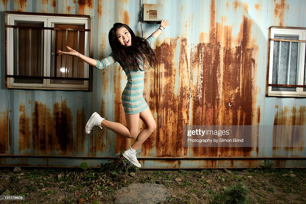 Woman jumping against of rusty wall. : Stock Photo