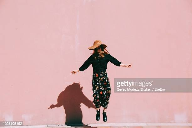 woman jumping against pink wall - rosa cor - fotografias e filmes do acervo