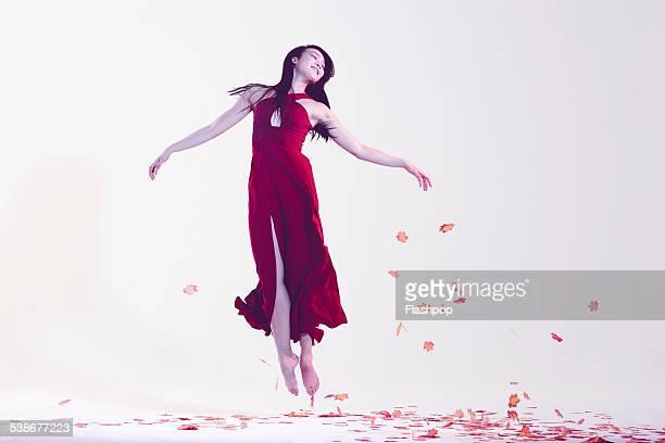 Woman jumping amongst leaves