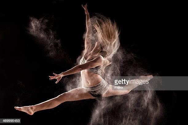 Frau springen und Tanzen in einer Wolke Pulverschnee