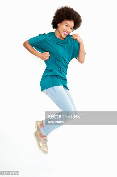 woman jumping and smiling - skinny jeans stock pictures, royalty-free photos & images