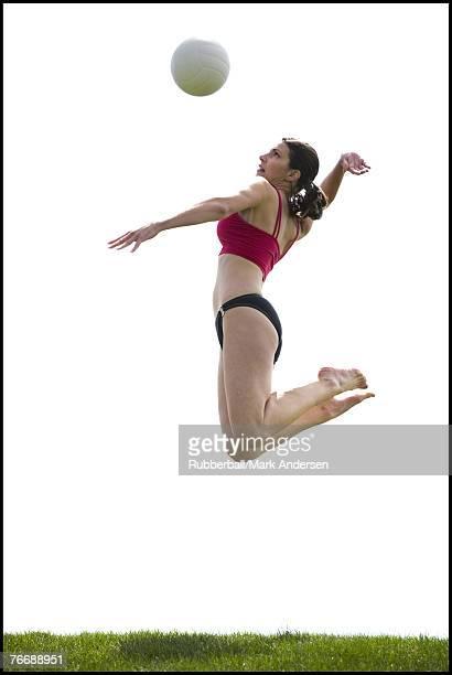 woman jumping and spiking volleyball outdoors - strandvolleyball spielerin stock-fotos und bilder