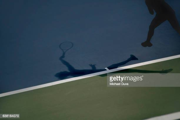 Woman jumping and striking tennis ball, playing tennis, noted in her shadow silhouette