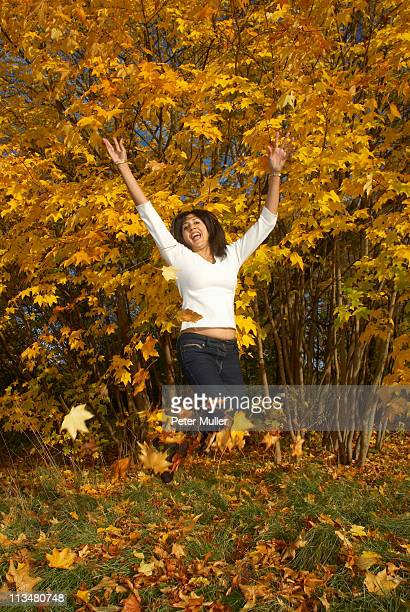 Woman jumping and throwing leaves