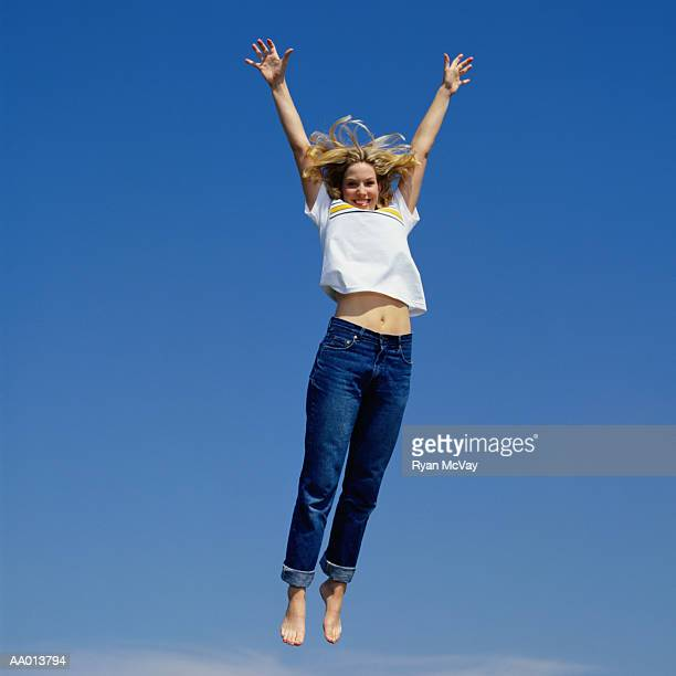 Woman jumping, arms overhead