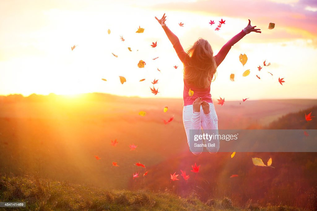 Woman Jumping at Sunset with Autumn Leaves : Stock Photo