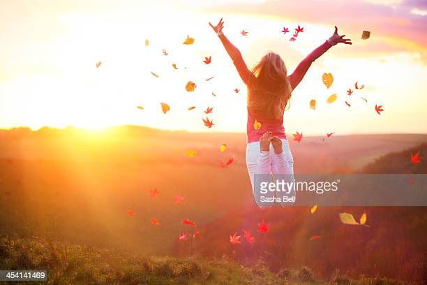 Woman Jumping at Sunset with Autumn Leaves