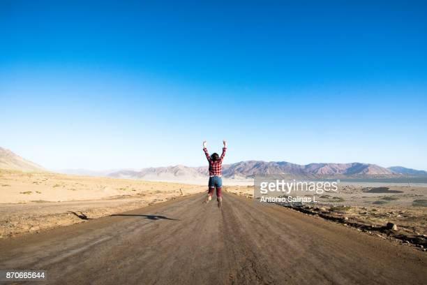 Woman jumping at the road Ataca Desert