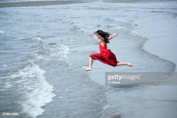 a woman jumping at the sea - eskapismus stock-fotos und bilder