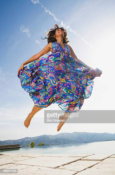 woman jumping by an infinity pool in a colorful dress smiling. - multi colored dress stock pictures, royalty-free photos & images