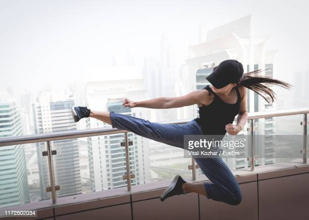 woman jumping by railing against buildings - martial arts stock pictures, royalty-free photos & images