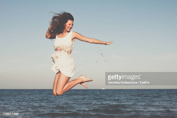 Woman Jumping By Sea
