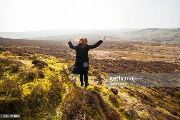 Woman jumping down hill in Haworth moors during a sunny day