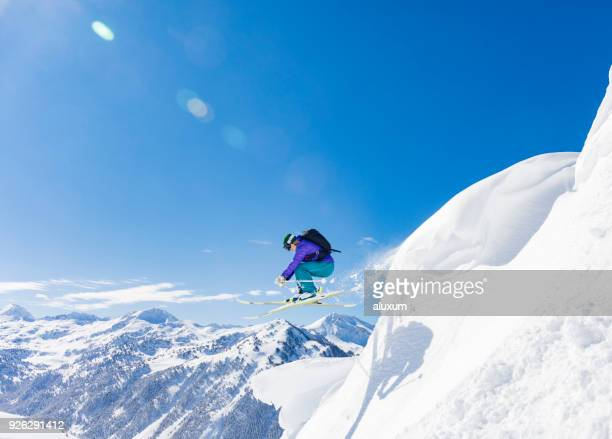 woman jumping during skiing day in the pyrenees baqueira beret catalonia spain - land feature stock pictures, royalty-free photos & images