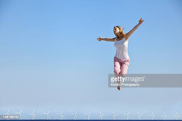 Woman jumping for joy over wind turbines