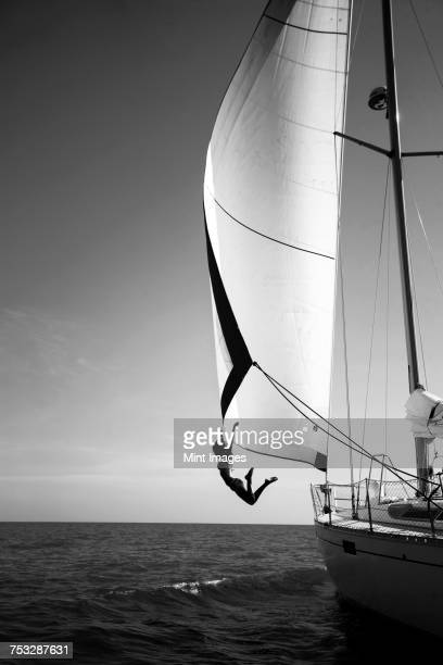 woman jumping from a yacht into the ocean. - voilier noir et blanc photos et images de collection