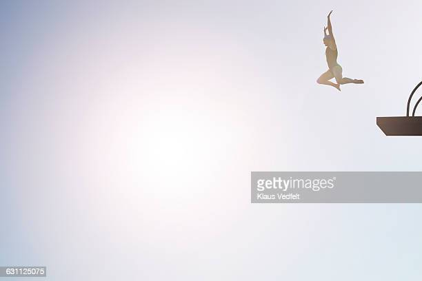 Woman jumping from diving platform at sunset