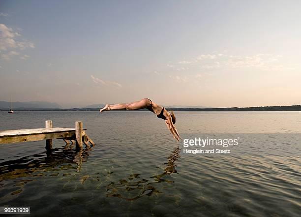 woman jumping from pier - lanzarse al agua fotografías e imágenes de stock