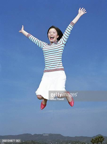 女性をジャンピング空気、腕 outreached 、ポートレート、低角度