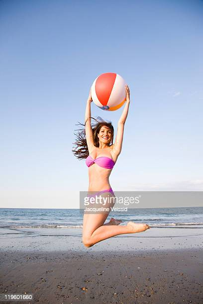 Woman jumping in air holding colorful beach ball