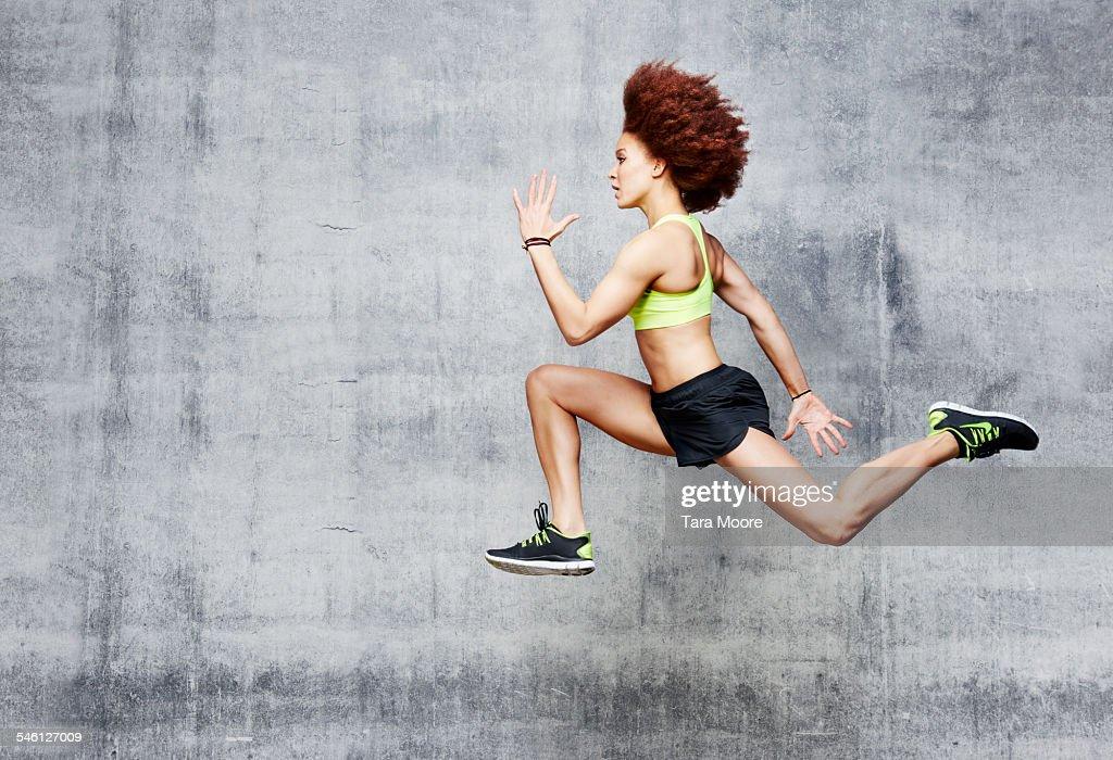 Woman jumping in air in urban studio : Stock Photo