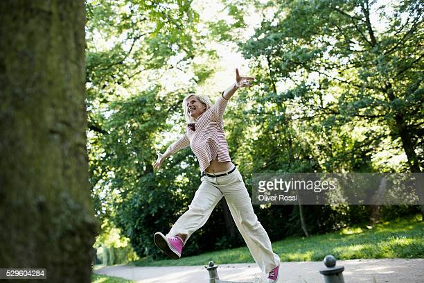 Woman jumping in air on park alley