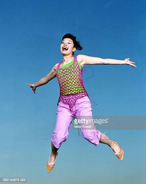 女性をジャンピング空気、ポートレート、低角度