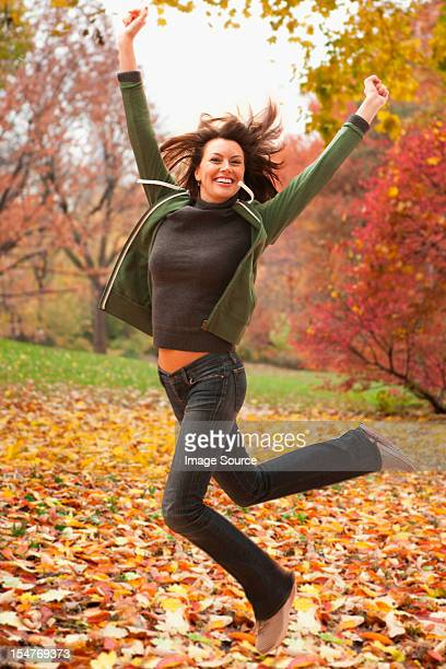woman jumping in autumn leaves - mid adult women stock pictures, royalty-free photos & images