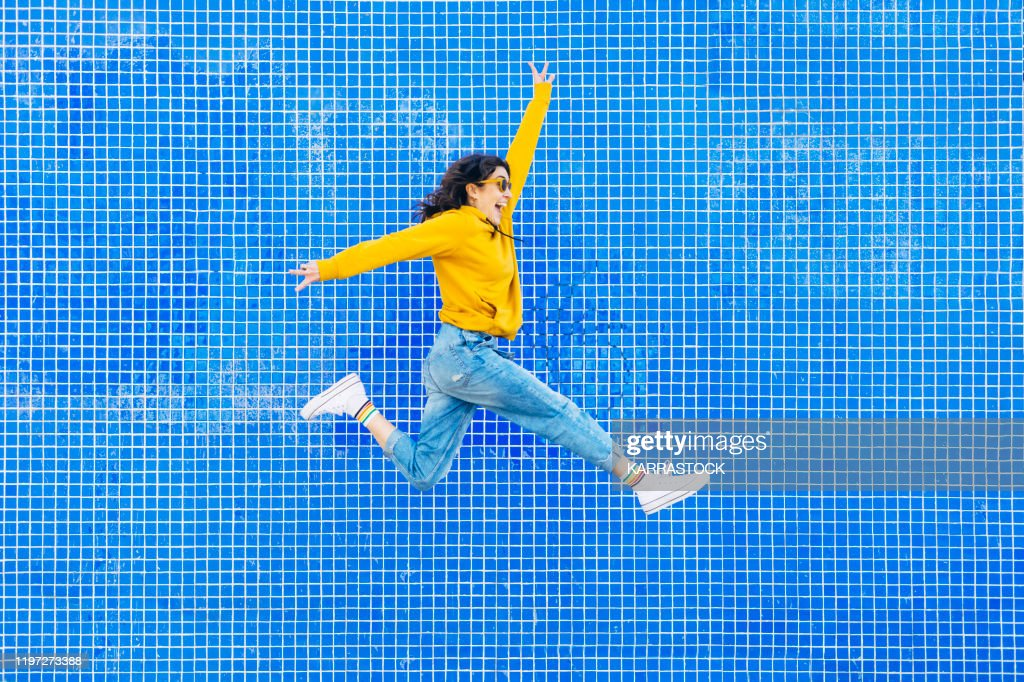 Woman jumping in front of a blue background : Stock Photo