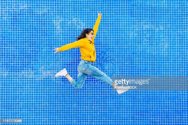woman jumping in front of a blue background - jumping stock pictures, royalty-free photos & images