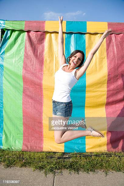 Woman jumping in front of colorful tent