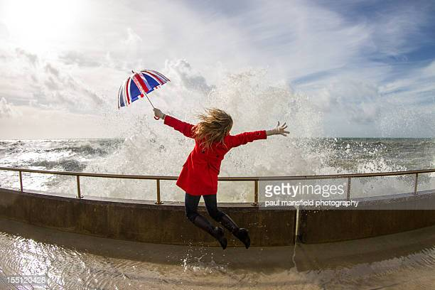 Woman jumping in front of crashing waves