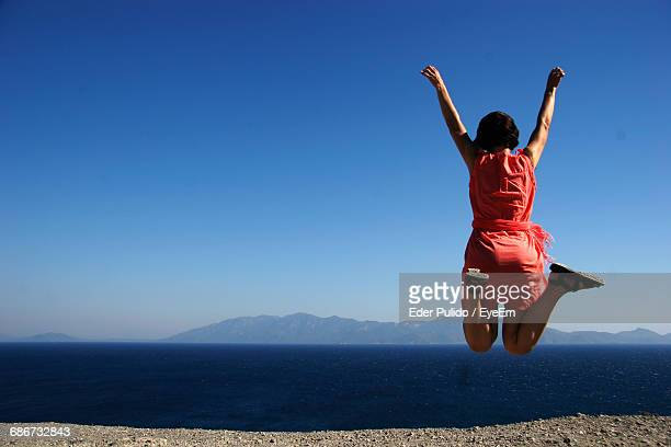 Woman Jumping In Front Of Sea Against Clear Blue Sky