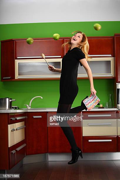 Woman jumping in kitchen, cherry wood panel