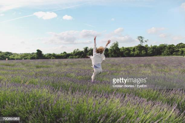 Woman Jumping In Lavender Field Against Sky