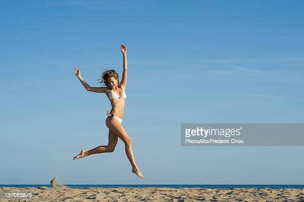 woman jumping in midair at the beach - femme maillot de bain photos et images de collection