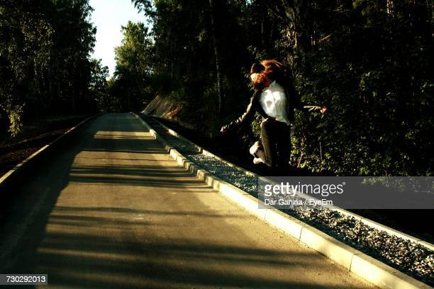 Woman Jumping In Mid-Air Over Footpath Amidst Trees At Park