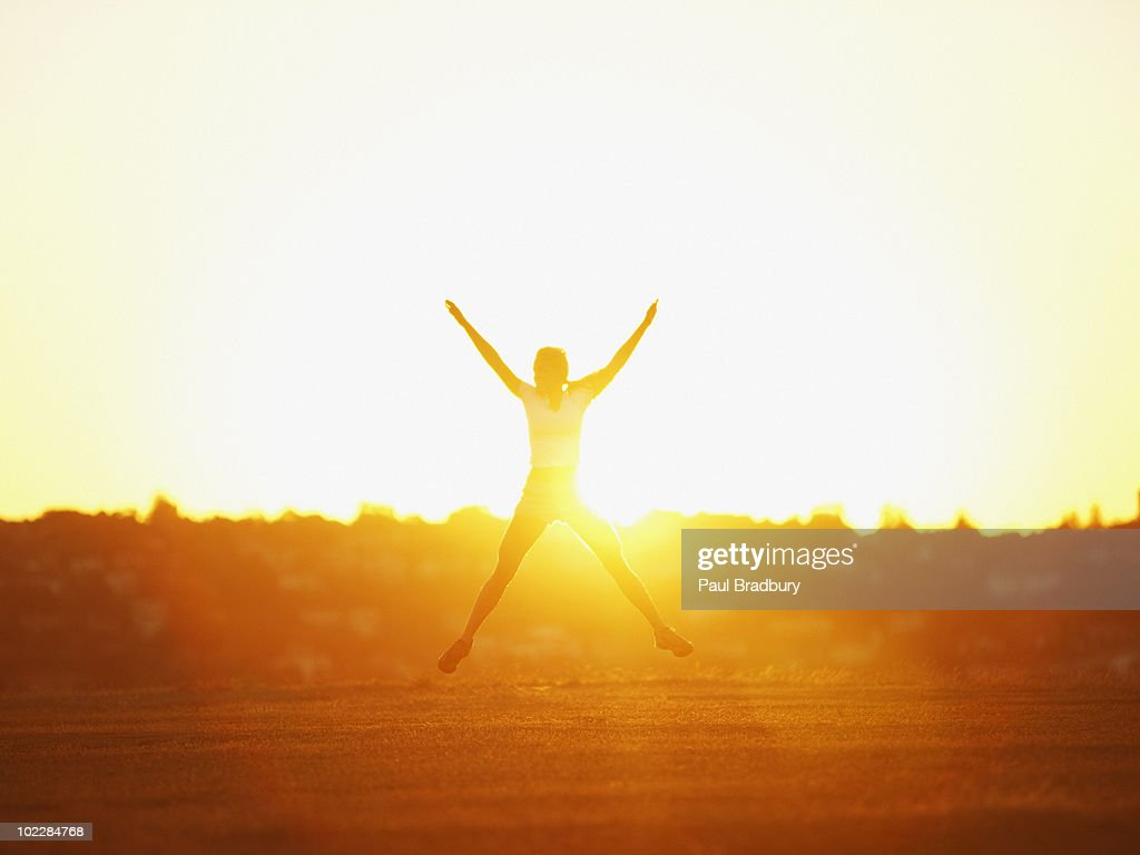 Woman jumping in park at sunset : Stock Photo