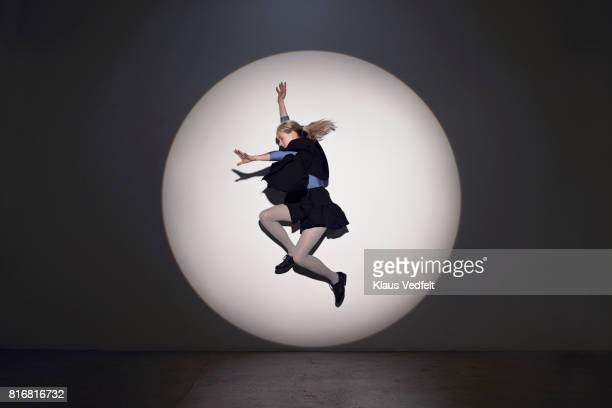 Woman jumping in round theatre spotlight, in studio with concrete floor