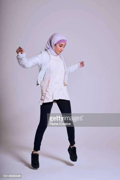 woman jumping in studio - modest clothing stock pictures, royalty-free photos & images