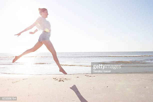 Woman jumping in sunset on beach