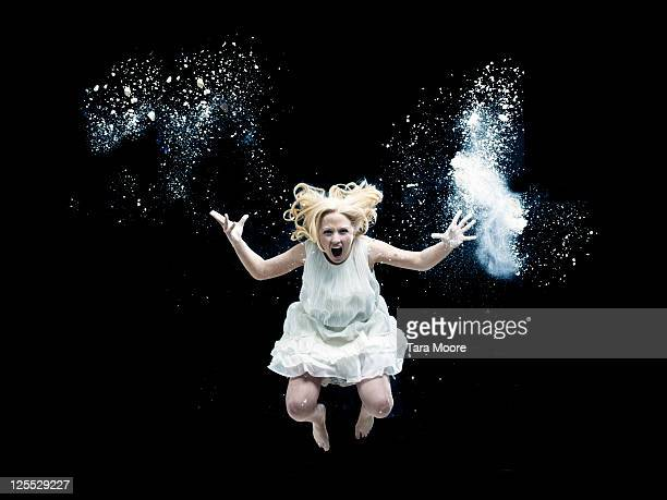 woman jumping in the air screaming with white dust