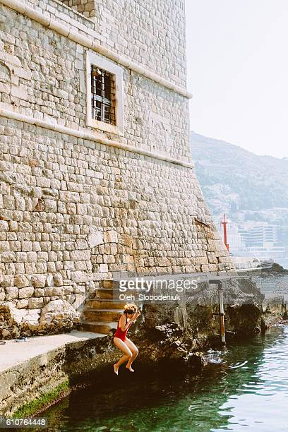 Woman jumping in  the water near Dubrovnik