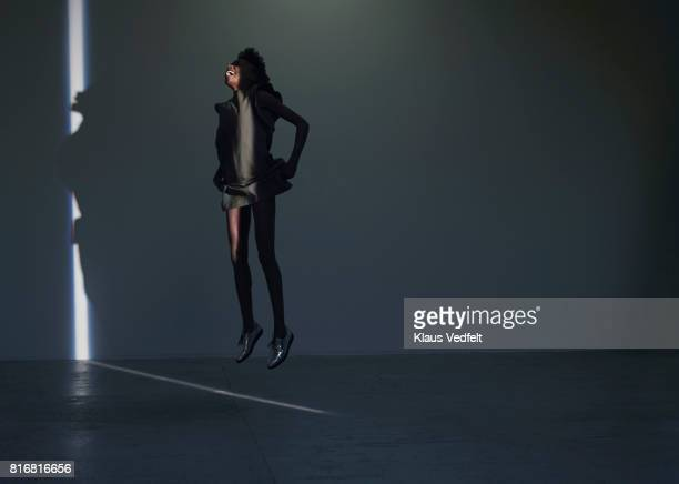 woman jumping in thin stripe og light, in studio with concrete floor - hovering stock pictures, royalty-free photos & images