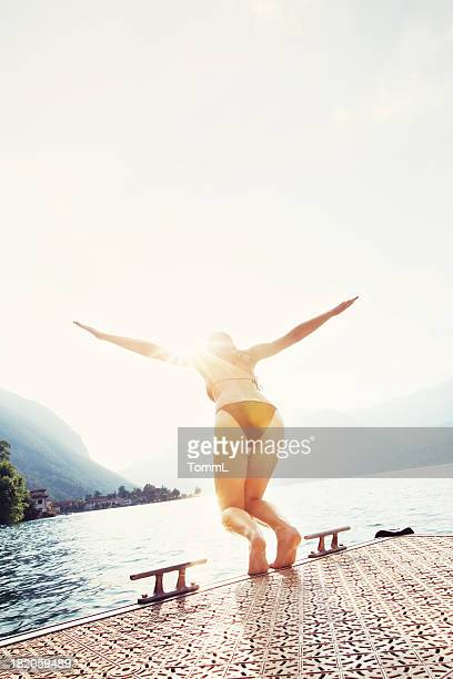 woman jumping into lake - taking the plunge stock photos and pictures